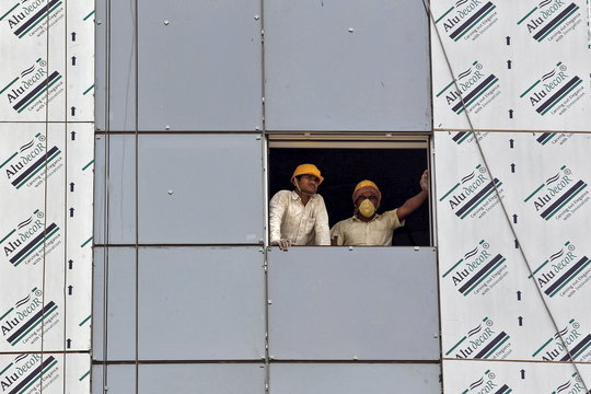 Labourers look out from a window of a data centre building under construction at the Gujarat International Finance Tec-City at Gandhinagar, in Gujarat