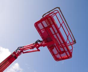 Red cherry picker machine in raised position, seen from below.