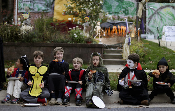 Children dressed in costumes eat pizza at the Flint family's annual Halloween block party in Silver Spring, Maryland