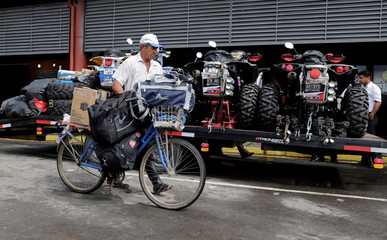 A man passes by the competition vehicles ahead of the Dakar Rally in Puerto Falcon