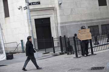 An Occupy Wall Street protester holds up a sign at the corner of Wall Street and Nassau Street in New York