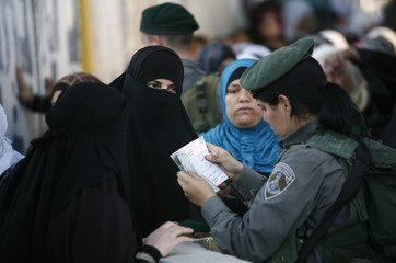 An Israeli border police woman checks the identification papers of a Palestinian woman at Israel's checkpoint in Bethlehem, on last Friday of Ramadan