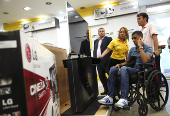 Shoppers shop for electronic goods at a Daka store in Caracas