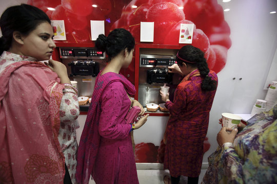 Women use a self-serve frozen yogurt at The Centaurus, a new shopping mall in Islamabad