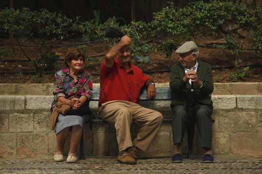 Pensioners rest on a bench in Alameda del Tajo park during the International Day of Older Persons in downtown Ronda