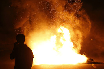 A French farmer makes a phone call in front burning tyres as they block the A1 Lille-Paris highway early in the morning in Seclin to protest against a squeeze in margins by retailers and food processors