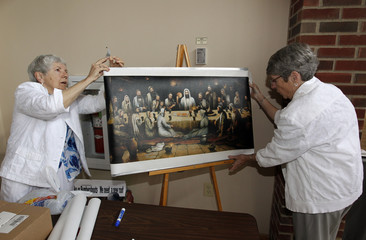 Duff and Turley prepare to hang picture of Last Supper that shows men, women and children, before celebration of Ordination of Rosemarie Smead as a priest, in Louisville