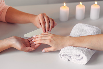 Spa salon.  Beautiful woman hands having nail filing with nail file by manicurist. Cosmetic procedure, manicure on female hand.
