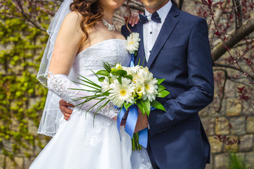 Hands of the groom and bride with bridal bouquet