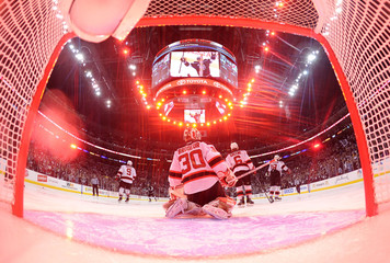 New Jersey Devils goalie Brodeur is bathed in red light as he kneels in his crease after Los Angeles Kings' Carter scored a goal during the second period in Game 6 of the NHL Stanley Cup final in Los Angeles