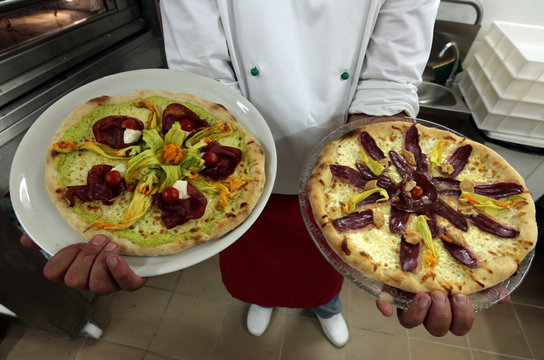 An adult student displays pizzas at the French pizzaiolo school in Cap D'Ail