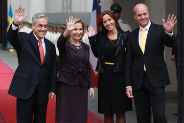 Chile's President Pinera and his wife wave with Swedish PM Reinfeldt and his wife before their meeting in Santiago