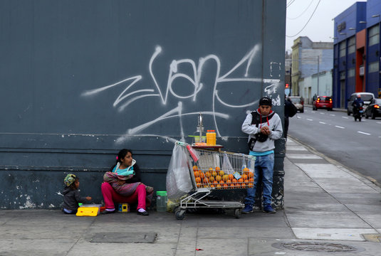 A man sells orange juice at a street in downtown Lima,