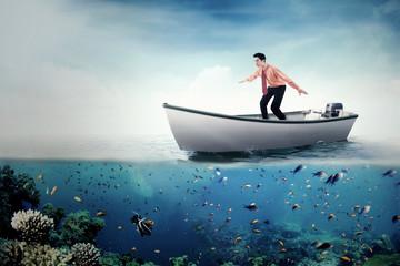 Young businessman driving boat at sea