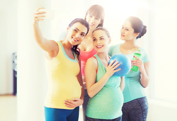pregnant women taking selfie by smartphone in gym