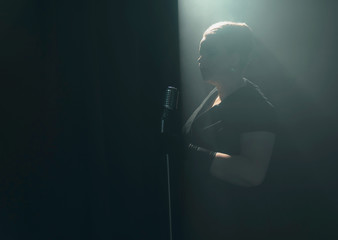 Silhouette of retro 1950s woman with microphone on smoky stage.