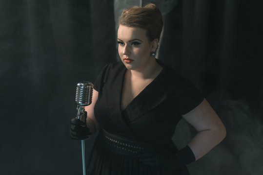 Retro 1950s female singer on smoky stage with black curtain.