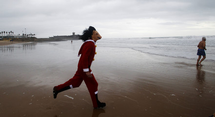 A reveller wearing a mask runs towards the sea as people participate in their first bath to celebrate the arrival of the new year at Carcavelos beach