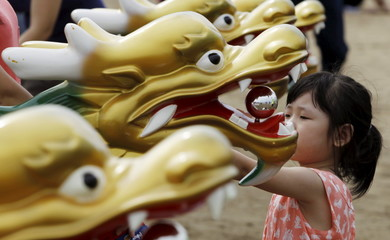 A girl looks at boat decorations during the Chinese dragon boat festival in the outskirts of Panama City