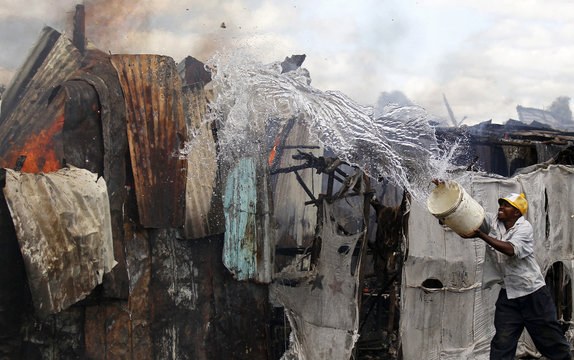 A trader attempts to extinguish fire with a bucket of water at the City Stadium open air market in Nairobi