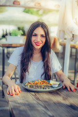 Young woman eating fresh tasty fish with french fries