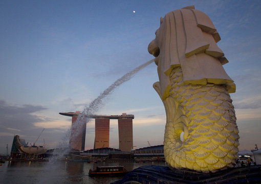 The Merlion statue overlooking the Marina Bay area spouts water as the Marina Bay Sands resort and casino is pictured in the background in Singapore