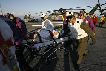 An injured U.S. citizen is carried to a waiting helicopter on board the USS Carl Vinson aircraft carrier for evacuation after being rescued from Port-au-Prince