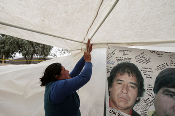 Clarina Segovia, sister of miner Victor Segovia who is among the 33 miners trapped inside the San Jose mine, hangs her brother's photo inside the tent in Camp Esperanza