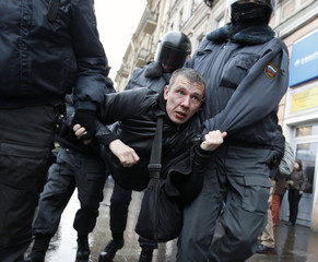 Policemen detain an activist during a rally to protest against violations at the parliamentary elections in St. Petersburg