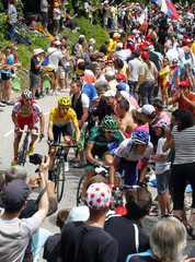 Sky Procycling rider and leader's yellow jersey Wiggins of Britain cycles past spectators during the 12th stage of the 99th Tour de France cycling race between Saint-Jean-de-Maurienne and Annonay-Davezieux
