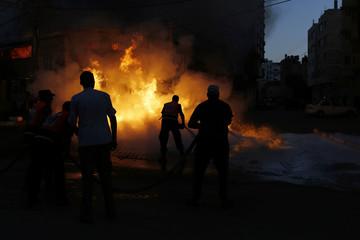 Firefighters try to extinguish a fire that witnesses say was caused by an Israeli air strike in Gaza City