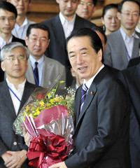Outgoing Japanese Prime Minister Naoto Kan receives a flower bouquet as he leaves his official residence in Tokyo