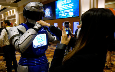 A man in a mechanized robotic costume kisses a woman's hand as she takes a picture of the encounter at the CES Unveiled event at CES in Las Vegas