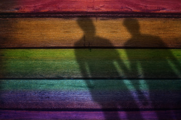 Blurred Shadow Shape of male lover on Rainbow Colored plank Wooden Background, Gay or Homosexual Concept