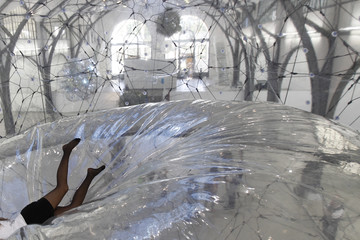 A museum staff member lies in installation that is part of Saraceno's Cloud Cities exhibition at Hamburger Bahnhof in Berlin