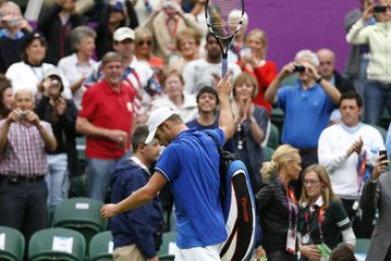 Roddick of the U.S. waves to spectators as he walks off court after being defeated by Serbia's Djokovic in their men's singles tennis match at the All England Lawn Tennis Club during the London 2012 Olympic Games