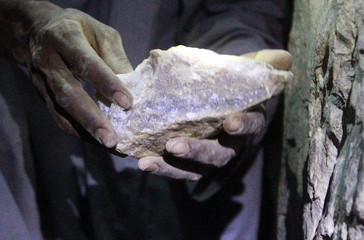 A gold mine worker displays a gold rock inside a local mine in Al-Ibedia locality at River Nile State