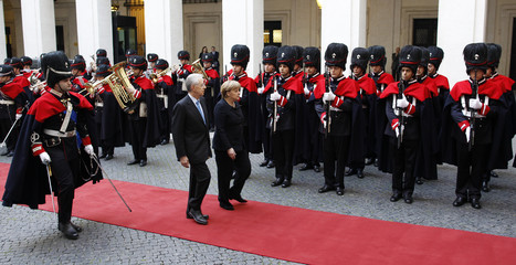 Italian PM Monti and German Chancellor Merkel review the honor guards at Chigi palace in Rome