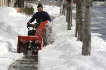 A man uses a snow blower to clear a side walk after a major winter storm swept over Washington