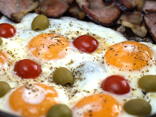 Fried eggs with bacon.olives and tomatoes a hearty breakfast.