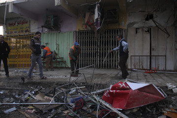 Residents inspect the site of a bomb attack in Baghdad