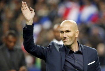 Former French captain Zinedine Zidane waves before the international friendly soccer match between France and Brazil at the Stade de France, in Saint-Denis