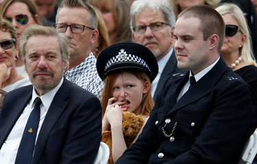 """A young in the families enclosure wears a police hat during a passing-out parade at the new """"Peel Centre"""" at the Metropolitan Police Academy in London"""