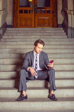 American Businessman texting on cell phone, sitting on stairs