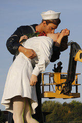 "A worker prepares the ""Unconditional Surrender"" sculpture by artist Seward Johnson outside the Memorial of Caen museum in Caen"