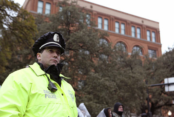 Dallas police officer John La Pietra stands guard at the spot where the first bullet hit President John F. Kennedy in 1963 during ceremonies commemorating the 50th anniversary of the death of Kennedy in Dealey Plaza in Dallas