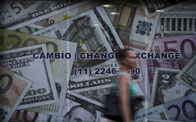 A woman walks past a currency exchange office in Sao Paulo
