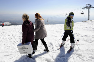 Electoral committee members leave with a mobile ballot box after voters from an alpine chalet cast their votes, below the Solisko peak in the High Tatras