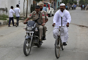An independent candidate Shyam Lal Gandhi rides bicycle next to security personnel on motorcycle during election campaign in northern Indian city of Amritsar