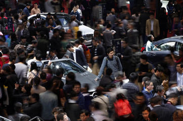 People looks at Mercedes-Benz cars during the 15th Shanghai International Automobile Industry Exhibition in Shanghai